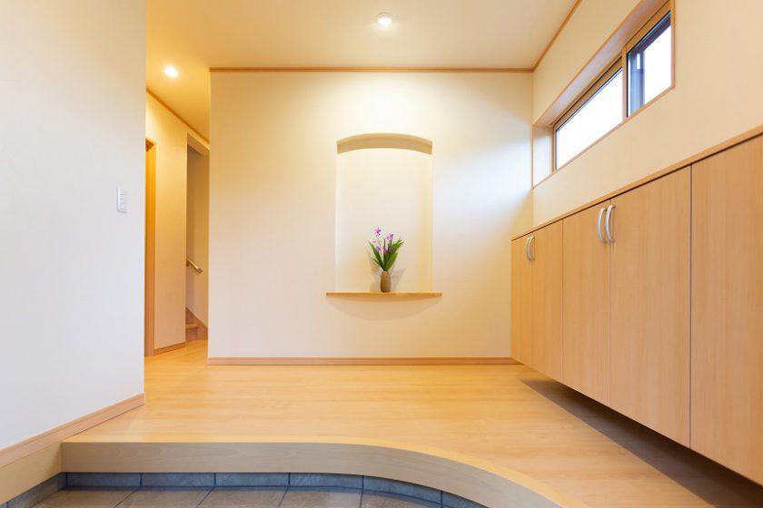玄関ホール:Rの上り框とメープル色で柔らかな雰囲気に。